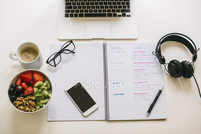 Laptop, headphones, notebook and salad on workplace — Stock Photo