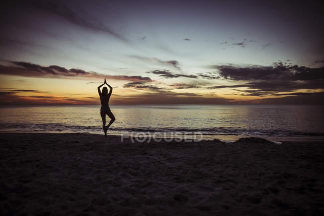 USA, Florida, Naples, Silhouette of woman doing yoga at beach, sunset — Stock Photo