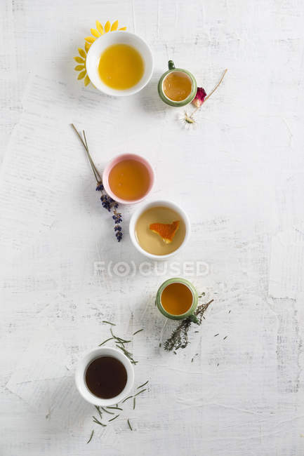Bowls of different sorts of honey on white surface — Stock Photo