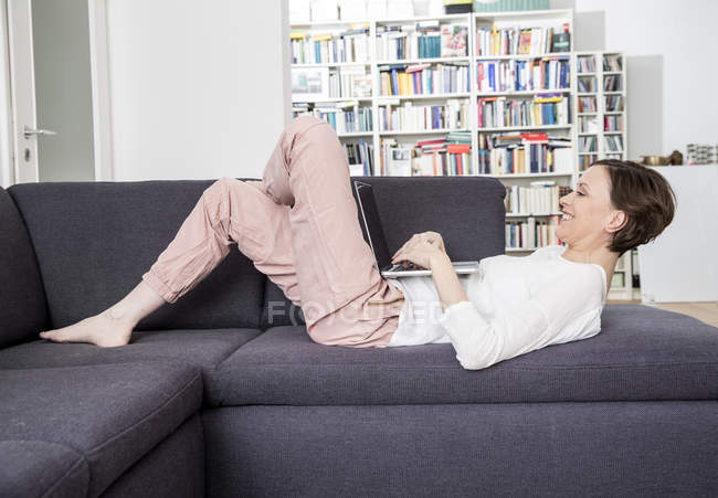 Happy woman lying on couch using laptop — Stock Photo