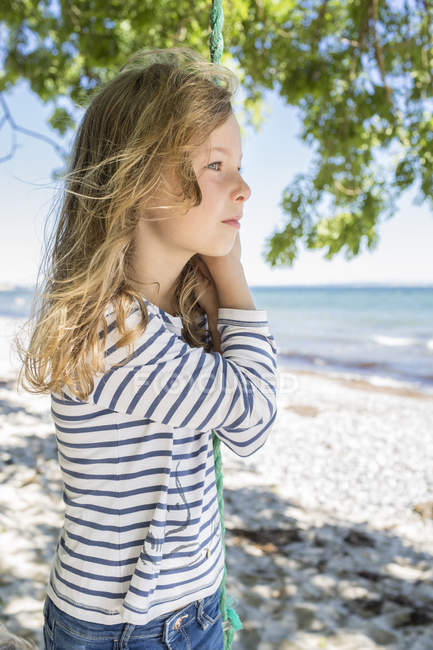 Portrait of blond girl standing next to swing on beach — Stock Photo