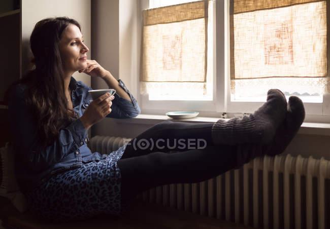 Мечтающая женщина с ногами на обогревателе пьет чашку чая, глядя в окно — стоковое фото