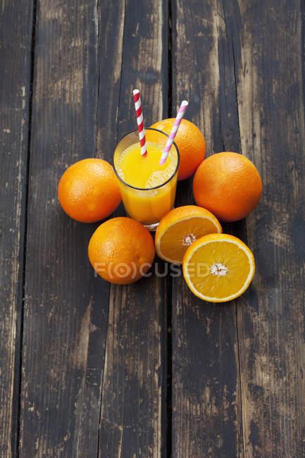 Les oranges entières et tranchées et verre de jus d'orange sur bois — Photo de stock