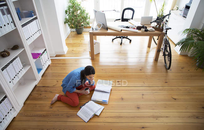 Donna seduta sul pavimento a leggere documenti — Foto stock