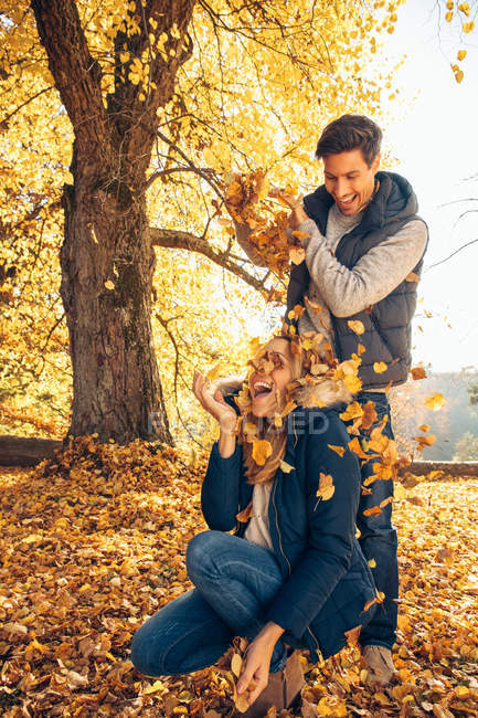 Couple having fun in autumnal forest — Stock Photo