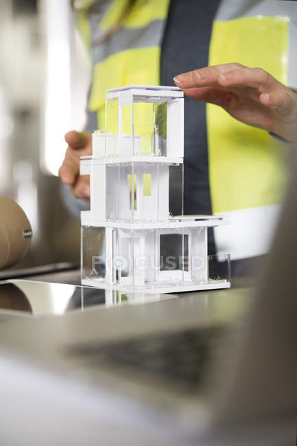 Close-up of woman wearing reflective vest with architectural model — Stock Photo