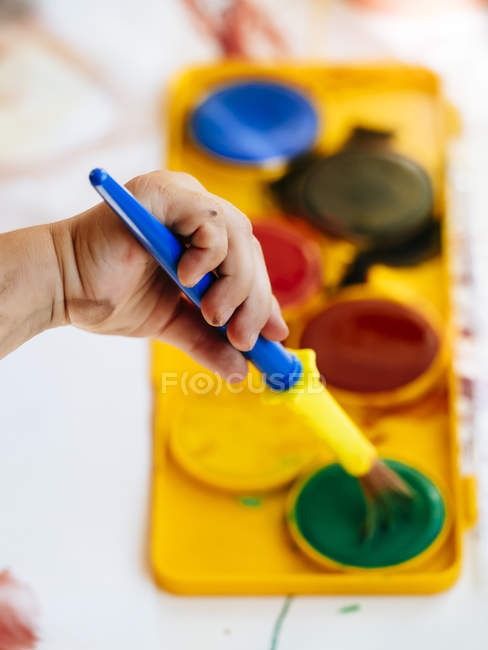 Hand of girl holding paintbrush and painting with watercolours — Stock Photo
