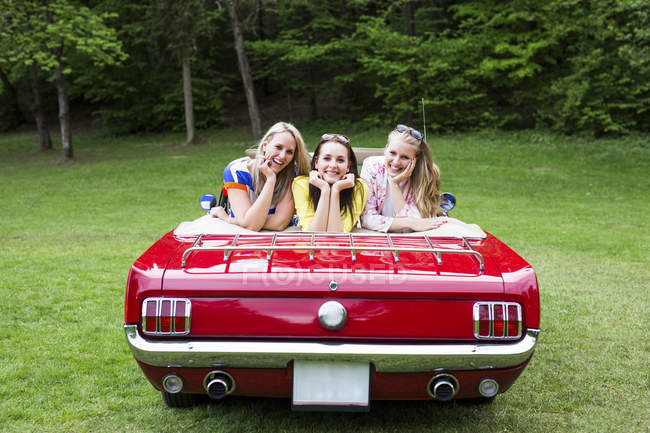 Three happy young women in a convertible parked on e meadow — Stock Photo