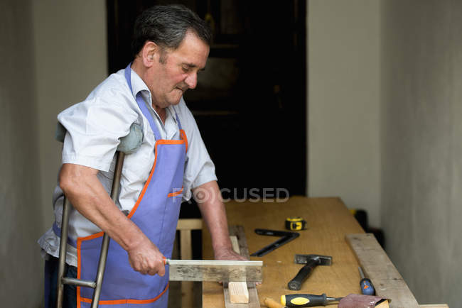 Senior man with crutch sawing piece of wood on workbench — Stock Photo