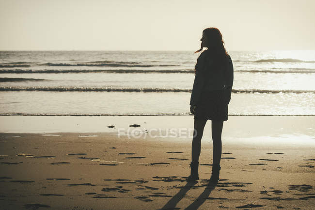 Young woman standing at seafront by twilight — Stock Photo