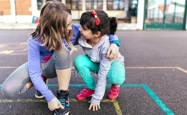 Две маленькие девочки, играя вместе на улице — стоковое фото