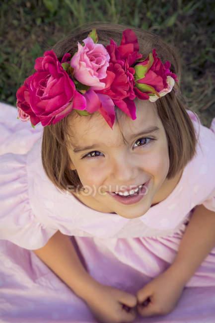 Портрет усміхнений дівчинка носіння квіти і погляд до камери — стокове фото