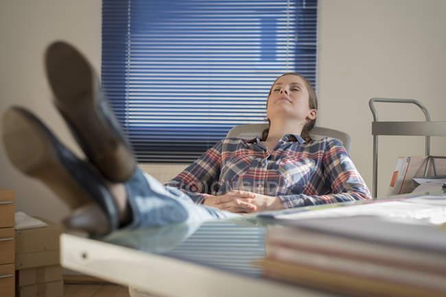 Jeune femme au bureau avec les pieds sur le bureau et les yeux fermés — Photo de stock