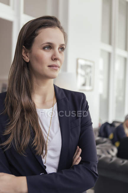 Portrait of young business woman with crossed arms looking at distance — Stock Photo