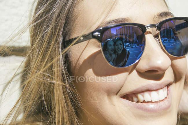 Друзья молодой женщины, отражающиеся в ее солнечных очках — стоковое фото