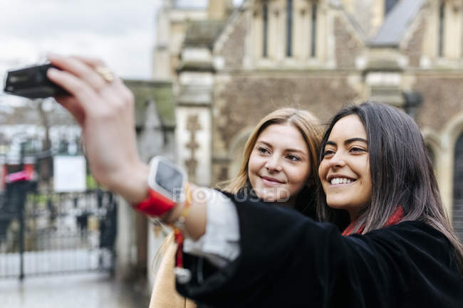 Two friends exploring the city, photographing selves in front of Southwark Cathedral, London, UK — Stock Photo
