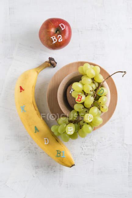 Plátano, manzana y uvas verdes, concepto de diferentes vitaminas - foto de stock