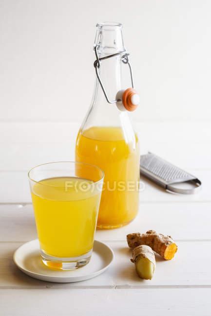 Detailansicht der Flasche und Glas Limonade mit Ingwer und Kurkuma-Wurzeln — Stockfoto