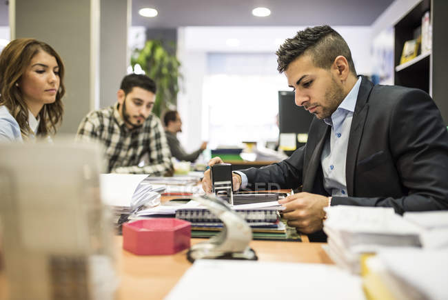 Escriturário de carimbar um documento no escritório com as pessoas — Fotografia de Stock