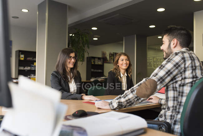 Three smiling colleagues in office sitting at desk — Stock Photo