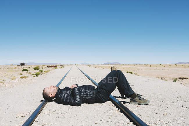 Bolivia, cementerio de trenes Uyuni, hombre acostado en las vías del tren - foto de stock
