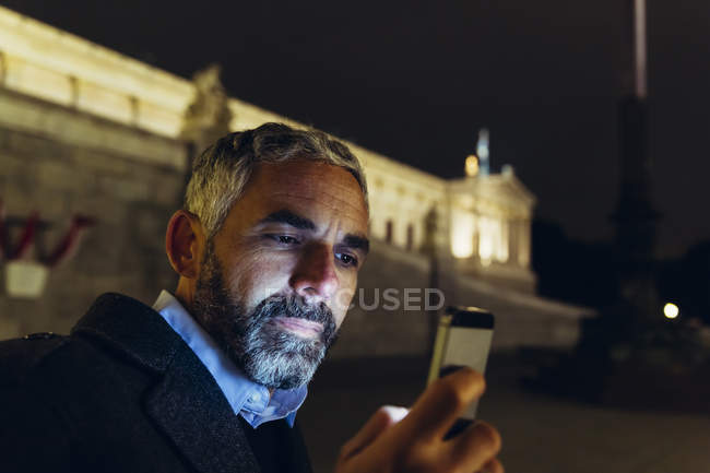 Portrait of man in front of parliament building looking at his smartphone by night — Stock Photo