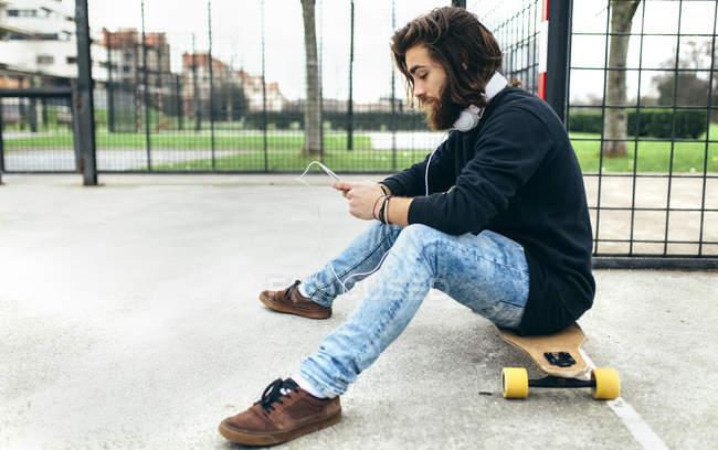 Бородатый молодой скейтбордист со смартфоном и наушниками — стоковое фото