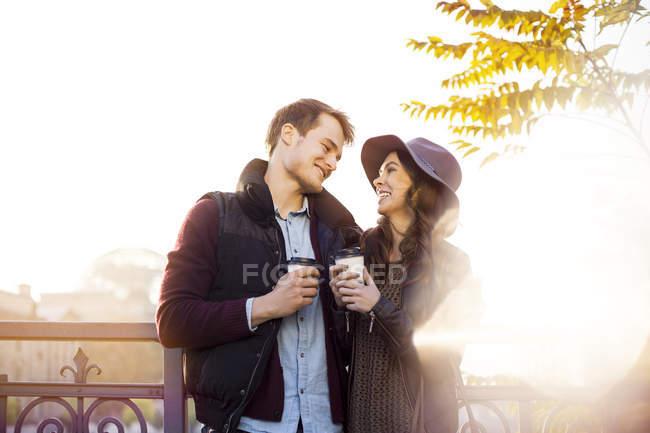 Улыбающаяся молодая пара с кофе на вынос — стоковое фото
