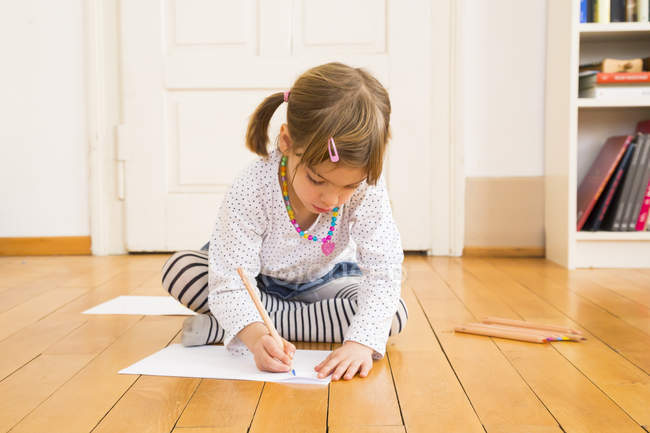 Girl sitting on wooden floor and painting with crayon — Stock Photo