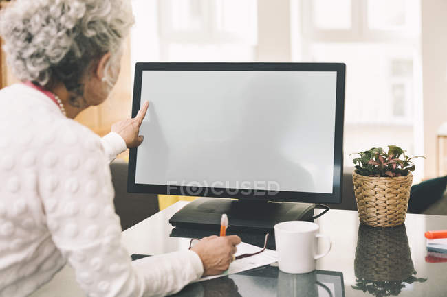 Over the shoulder shot of elderly woman using a desktop computer at home — Stock Photo