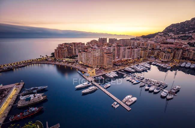Monaco, Monte Carlo at dusk and moored boats at dock — Stock Photo