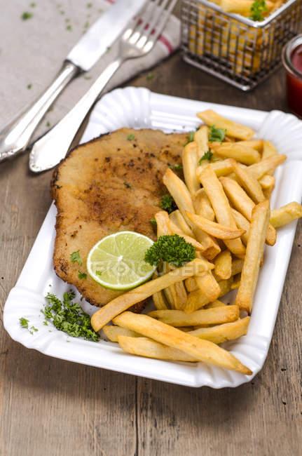 Nahaufnahme von paniertem Kalbfleisch mit Limetten und Pommes auf dem Teller — Stockfoto
