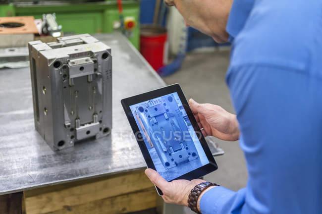 Mann mit digital-Tablette Prüfung Metall Werkstück — Stockfoto