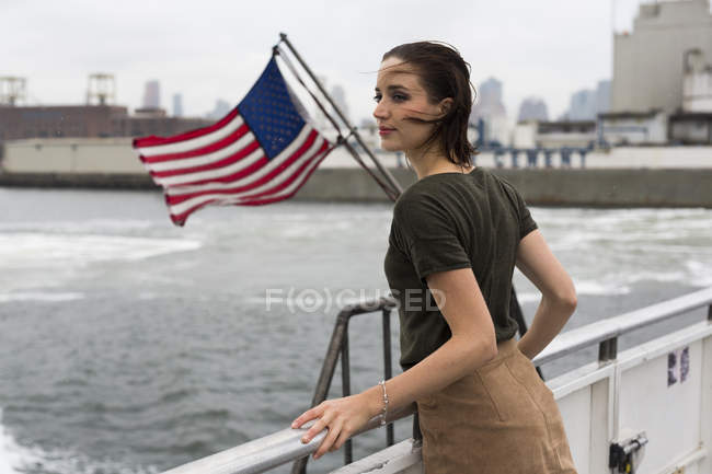 USA, New York City, young woman standing on an excursion boat on a windy day — Stock Photo