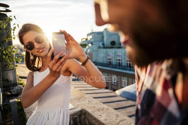 Souriante jeune femme prenant une photo de son petit ami sur un toit-terrasse — Photo de stock