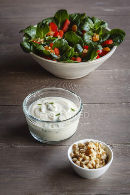 Bowl of mixed salad, silken tofu dressing and bowl of walnuts on wood — Stock Photo