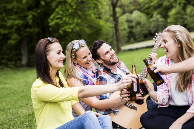 Happy friends clinking beer bottles in park — Stock Photo