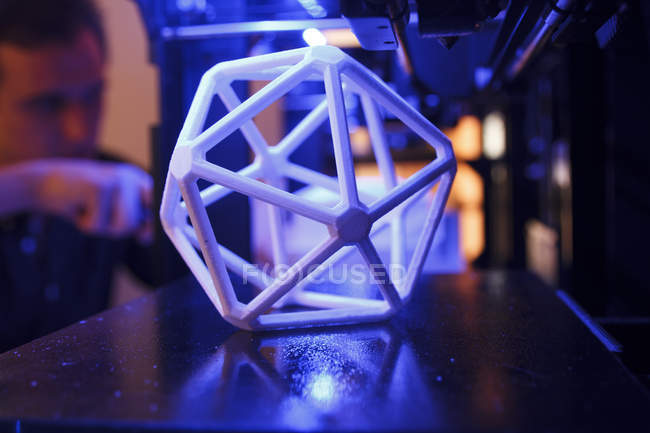 3D geometric figure on the platform of a 3D printer with a man in the background — Stock Photo