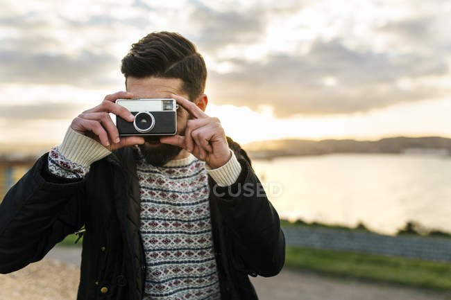 Bearded man with an old camera taking a picture of viewer — Stock Photo