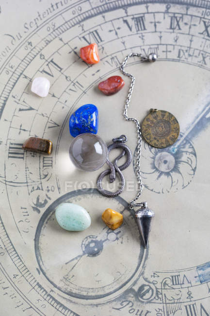 Semiprecious stones, pendulum, pendant and crystal ball on horoscope circle — Stock Photo