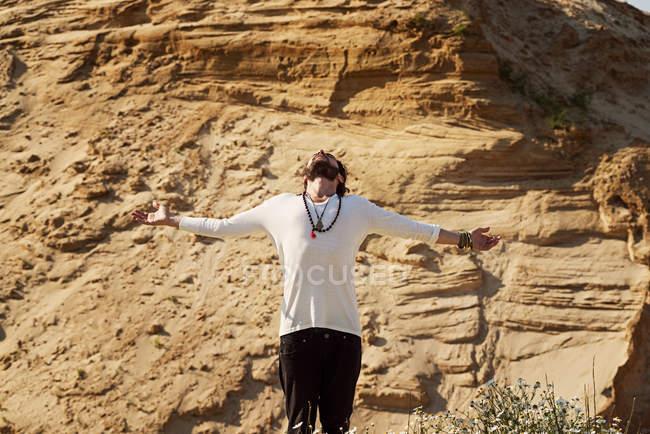 Homme debout avec les bras tendus — Photo de stock