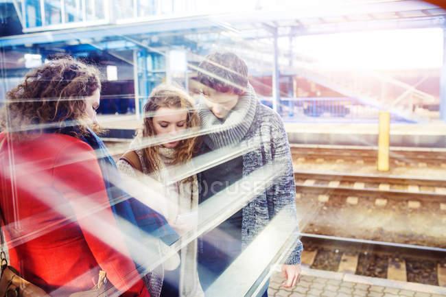 Trois amis, debout sur le quai de la gare avec sentiers de lumière — Photo de stock