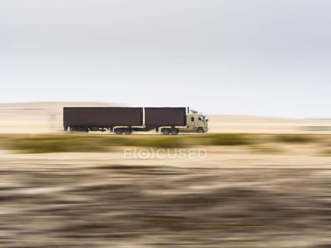 Namíbia, Erongo, caminhão dirigindo rápido na estrada costeira C34 durante o dia — Fotografia de Stock
