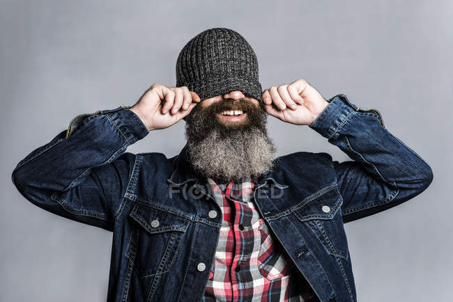 Bearded man putting on woolly hat and covering his eyes — Stock Photo