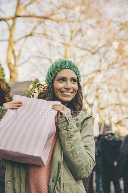 Happy woman holding gift bag at Christmas Market — Stock Photo
