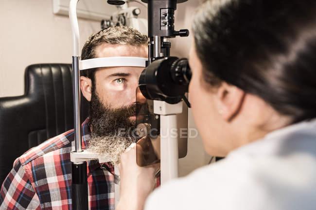 Optometrist examining eyes of a bearded man — Stock Photo