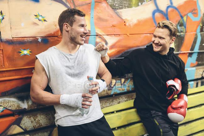 Два боксера разговаривают после тренировки перед граффити — стоковое фото