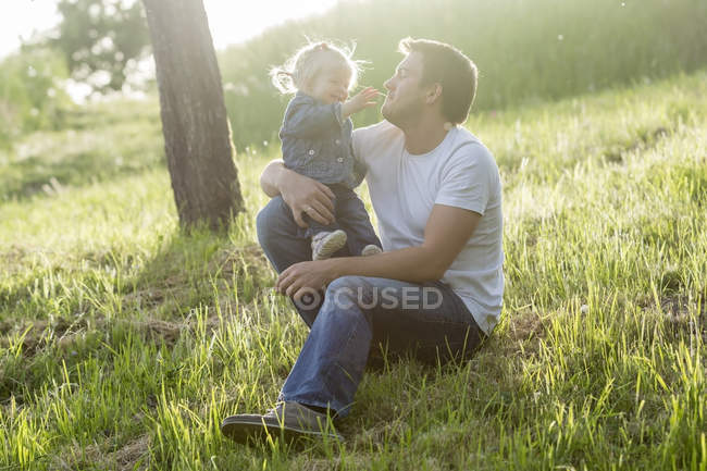 Father playing with his little daughter on a meadow — Stock Photo