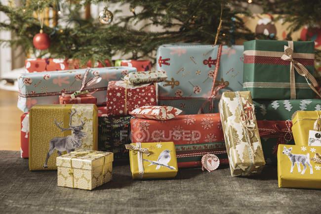 Christmas presents under tree indoors — Stock Photo