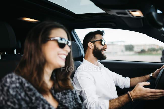 Молода пара посміхаючись, їздили на машині — стокове фото